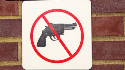 gun free zone sign on brick wall
